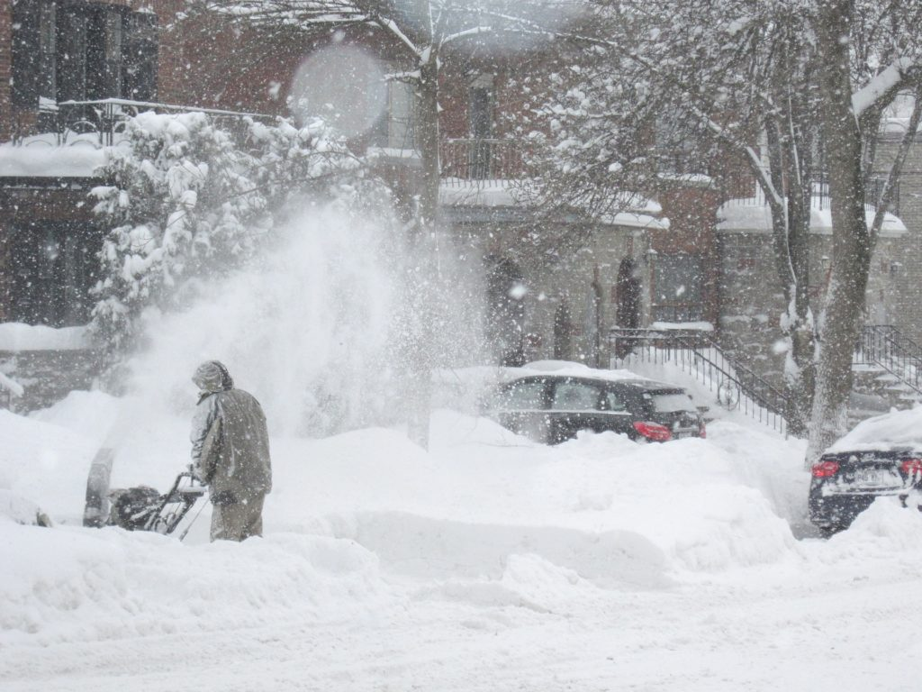 man clearing snow with a snowblower in a blizzard